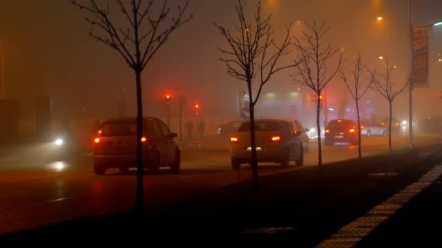 トラフィック ライトと霧の夜の街の十字路 - electric lamp点の映像素材/bロール