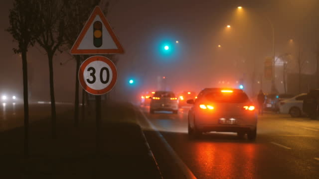 Traffic lights and crossroad in a foggy night in the city