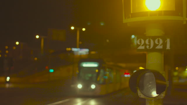 traffic lights and yellow lighting at outskirts of a big city at night. a defocus tram crosses the shot from right to left. - 後ろボケ点の映像素材/bロール