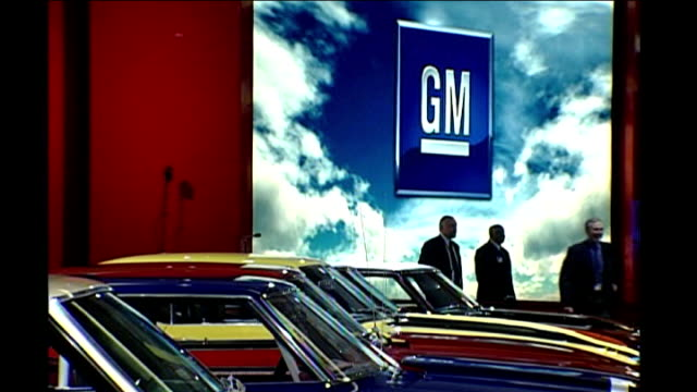 EXT Traffic lights turning from red to green with GM high rise building in background Line of cars with GM Motors logo sign in background Various of...
