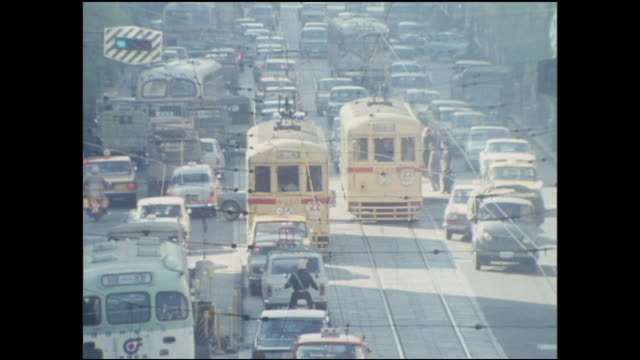 traffic maneuvers around a tramcar on the last day of operation for the toden ginza line in tokyo. - showa period stock videos & royalty-free footage