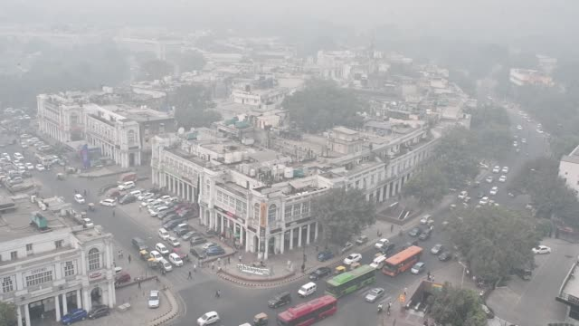 Traffic move along a road as buildings stand shrouded in smog in New Delhi India on Saturday Nov 11 2017