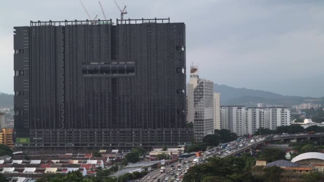Traffic move along a road past Mah Sing Group Bhd's M City development left in Kuala Lumpur Malaysia on Wednesday Aug 2 Traffic move along a highway...