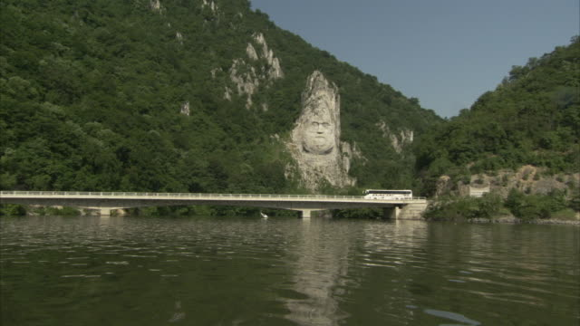 traffic moves across a bridge over the danube river, passing the sculpture of decebalus, romania. - river danube video stock e b–roll