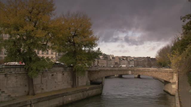 vidéos et rushes de traffic moves across a small bridge on the river seine. available in hd. - canal eau vive