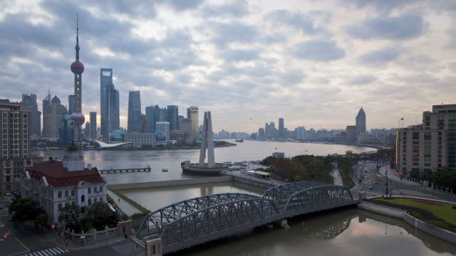Traffic moves across the Waibaidu Bridge and boats move along the Huangpu River in Shanghai, China.