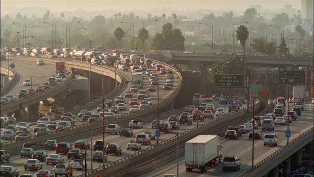 traffic moves along a busy freeway. - hart arbeiten stock-videos und b-roll-filmmaterial