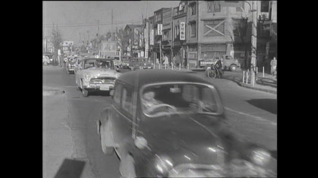 traffic moves along a congested street / shot at city street in tokyo on january 31, 1959 - 1950~1959年点の映像素材/bロール