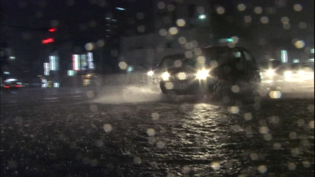 Traffic moves along a flooded street at night.