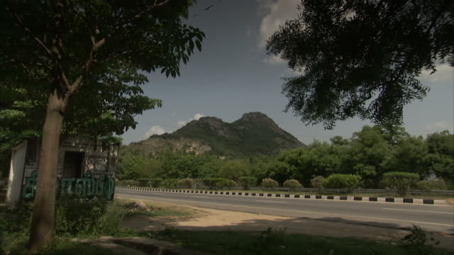 Traffic moves along a highway with lush mountain looming in the distance.