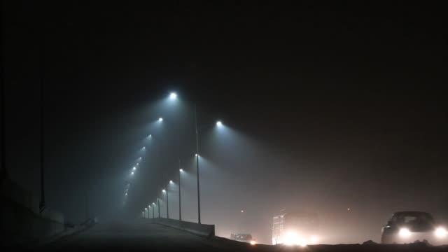 traffic moves along a road shrouded in smog at night in new delhi, india, on friday, nov. 10, 2017 - ナイトイン点の映像素材/bロール