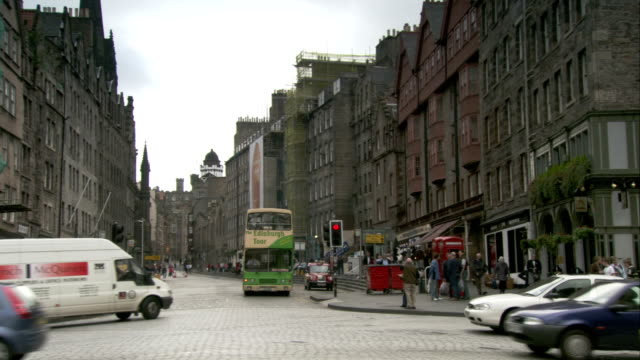 traffic moves along a street in edinburgh near the royal mile. available in hd. - royal stock videos and b-roll footage