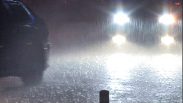 Traffic moves along a street in the heavy rain at night.