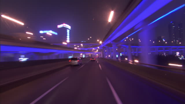 traffic moves along an illuminated tunnel at night. - tunnel stock videos & royalty-free footage