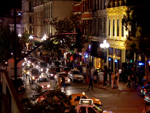 Traffic moves along busy San Diego street at night including yellow taxis pedestrians cross road in background