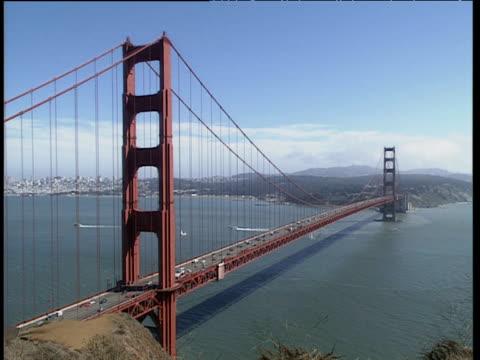 Traffic moves along Golden Gate Bridge. Boats sail on calm seas below. Blue skies San Francisco