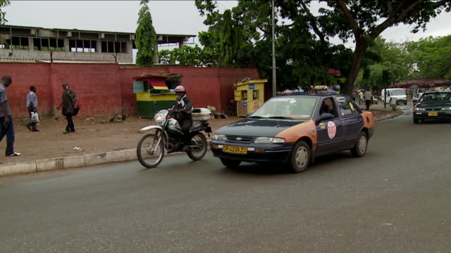 Traffic moves along the city streets of Accra, Ghana. Available in HD.