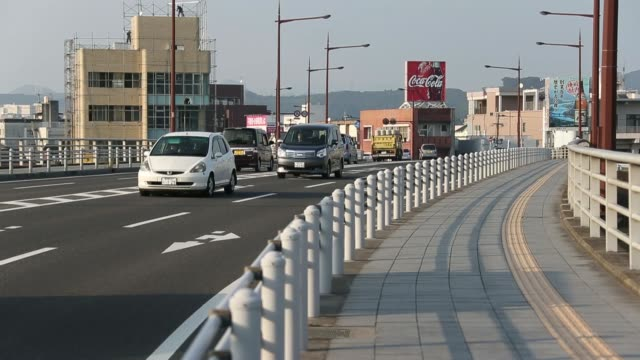 Traffic moves along the main street in Satsumasendai Kagoshima Prefecture Japan on Monday Oct 27 A woman walks along a shopping street Traffic moves...