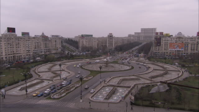 vídeos y material grabado en eventos de stock de traffic moves around a large roundabout in front of the palace of parliament in bucharest. available in hd - rumania