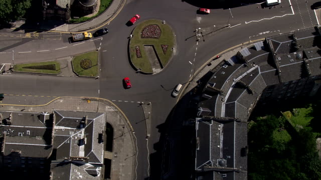 Traffic moves around a traffic circle in a residential neighborhood. Available in HD.