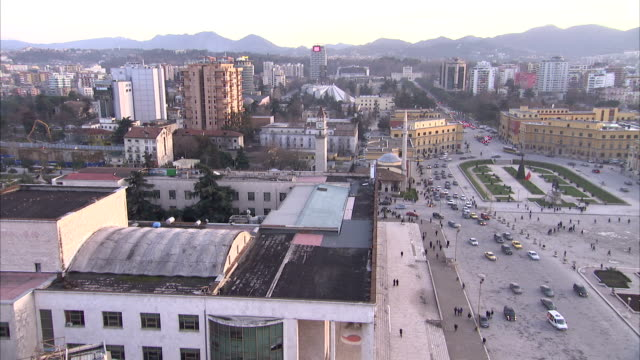 Traffic moves around Skanderberg Square, passing the Skanderberg Monument and Et'hem Bey Mosque, Tirana. Available in HD.