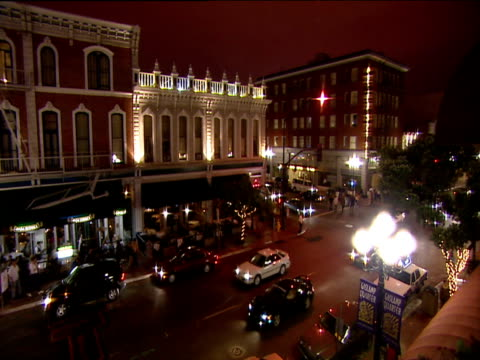 Traffic moves down San Diego street at night past ornate buildings and street lamps
