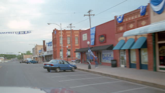 traffic moves down the main street in a small texas town. - southwest usa stock-videos und b-roll-filmmaterial