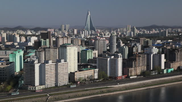 traffic moves on a street along the taedong river near downtown pyongyang, north korea. - pyongyang stock videos and b-roll footage