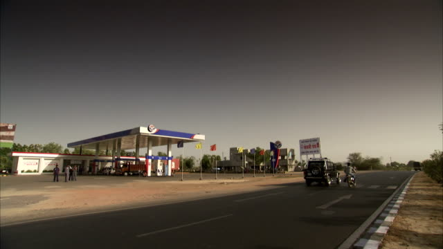 Traffic moves past a rural gas station.