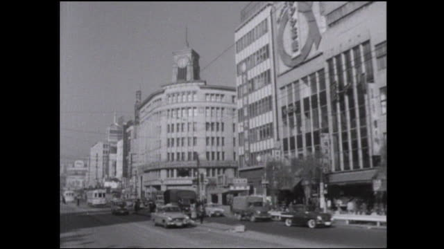 traffic moves past stores near a ginza intersection. - showa period stock videos & royalty-free footage