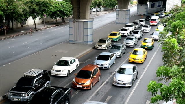 Traffic moves slowly along a busy road in Bangkok, Thailand