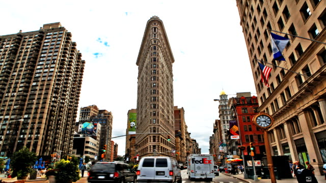 traffic moves through an intersection near the flat iron building in new york city. - hair straighteners stock videos and b-roll footage