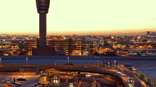 Traffic moves underneath an elevated airport runway past a control tower in Phoenix, Arizona.