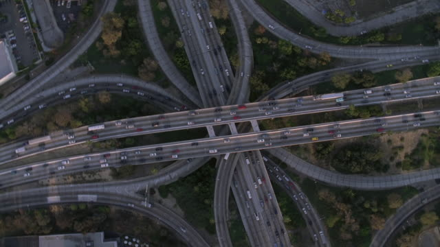 vídeos de stock e filmes b-roll de aerial traffic moving along the los angeles freeway interchange while the sunrise silhouettes the downtown skyline in the horizon / california, united states - trevo de quatro folhas