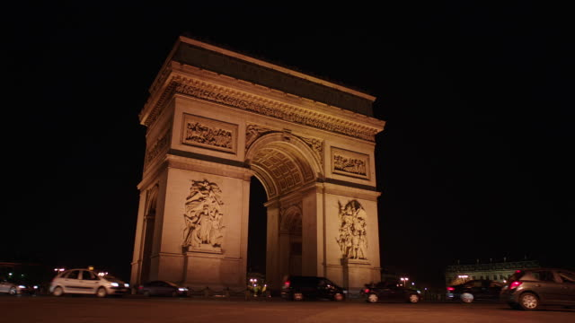 WS Traffic moving around Arc de Triomphe at night / Paris, France