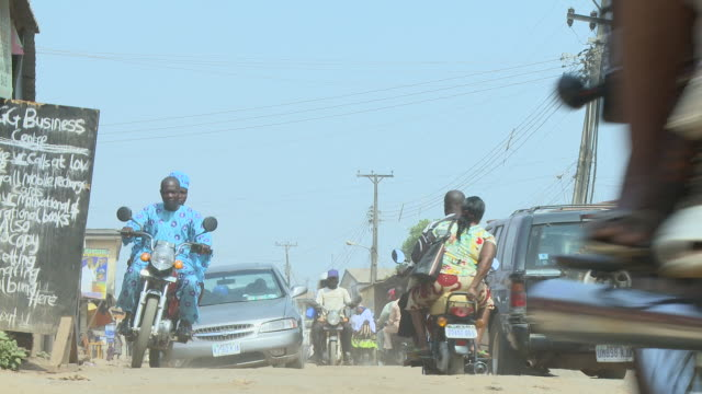 la traffic moving down uneven dirt road nigeria is home to nearly 200 million people which has earned it the name giant of africa it is an oil rich... - uneven stock videos & royalty-free footage