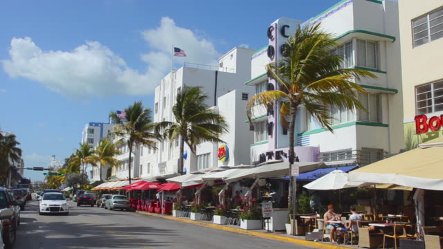 MS Traffic moving in front of beach ocean drive restaurants at Pastel Retro Art Deco District / Miami, Florida, United States