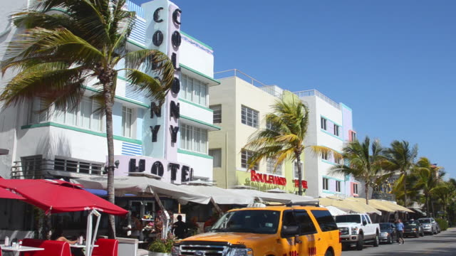 ms traffic moving in front of beach ocean drive restaurants at pastel retro art deco district / miami, florida, united states - アールデコ点の映像素材/bロール