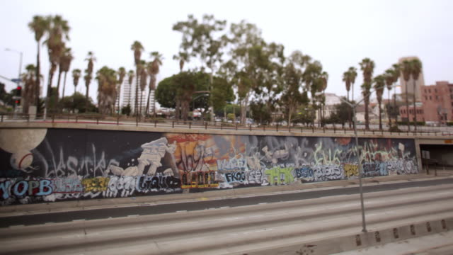 MS PAN Traffic moving in front of graffiti wall / Los Angeles, California, United States