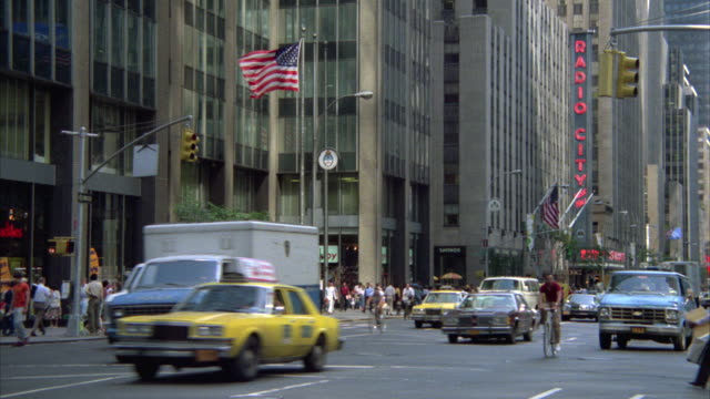 ms tu zi traffic moving in front of modern glass office building - radio city music hall stock videos & royalty-free footage