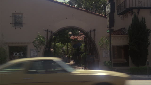 ms traffic moving in front of small spanish style office building or restaurant with wrought iron gate and arched entrance - small office stock videos & royalty-free footage