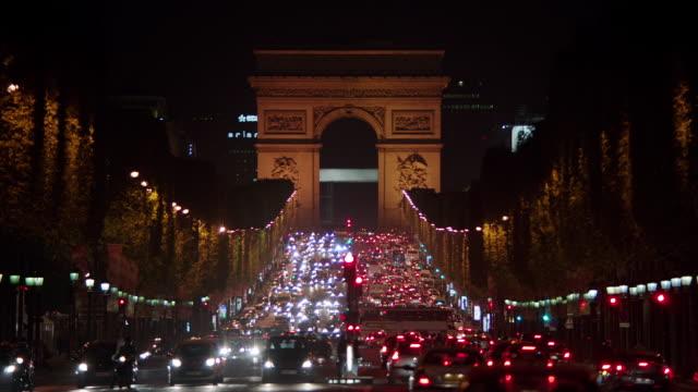 vídeos de stock e filmes b-roll de ms r/f traffic moving on avenue des champs-elysees at night, arc de triomphe in background / paris, france - arco caraterística arquitetural