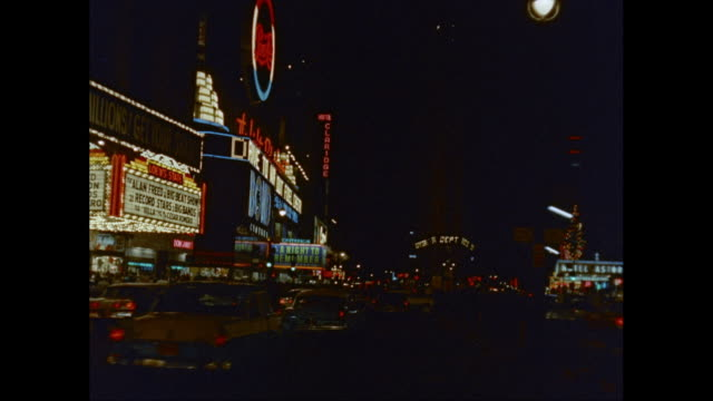 vidéos et rushes de ws traffic moving on broadway with illuminated commercial signs at night / new york city, new york state, united states - 1960
