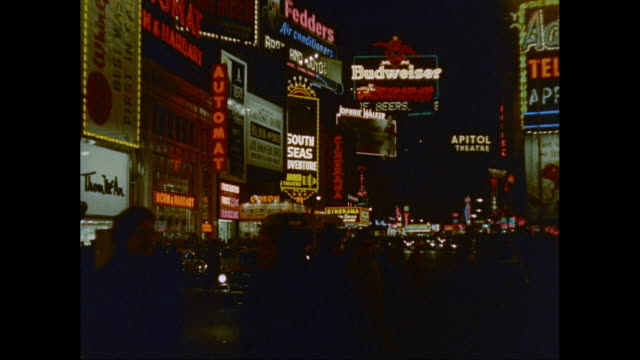 WS Traffic moving on Broadway with illuminated commercial signs at night / New York City, New York State, United States