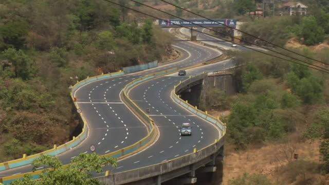 ws traffic moving on highway, mountain in background / mumbai, maharashtra, india - main road stock videos & royalty-free footage