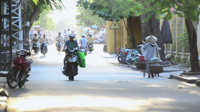 MS Traffic moving on Hoi An Street in late afternoon sunshine / Hoi An, Quang Nam, Viet Nam