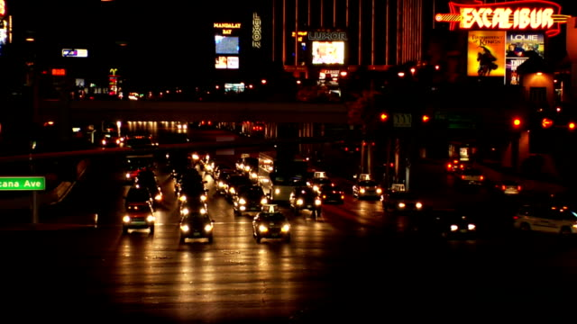 traffic moving on las vegas blvd west tropicana avenue cross streets traffic taking turns going lights of partial excalibur hotel casino on the strip... - las vegas crosses stock-videos und b-roll-filmmaterial