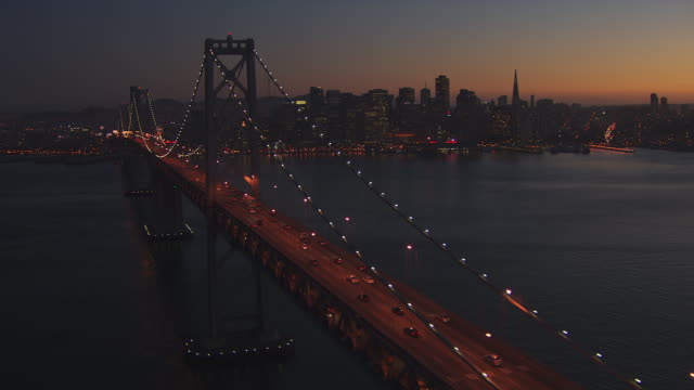 WS ZO POV Traffic moving on Oakland Bay Bridge at dusk with city / San Francisco, California, United States