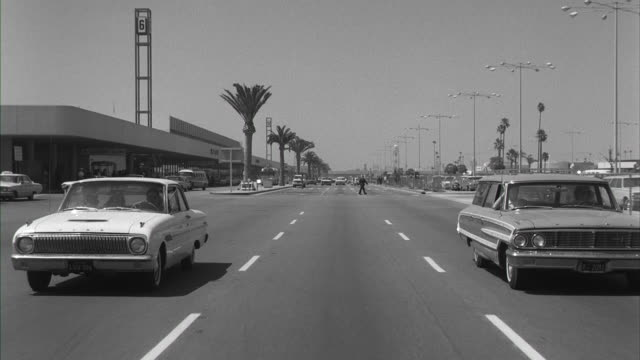 vidéos et rushes de ms pov traffic moving on road at los angeles international airport - 1964