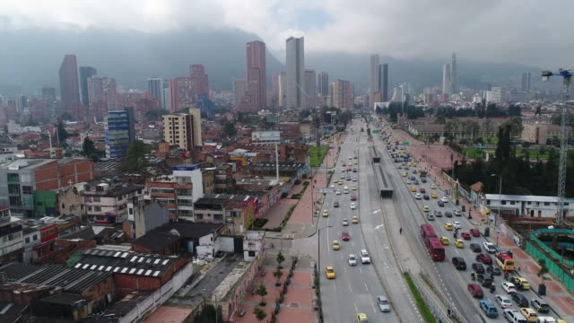 traffic moving on road by buildings in city, bogota, colombia - bogota stock videos & royalty-free footage